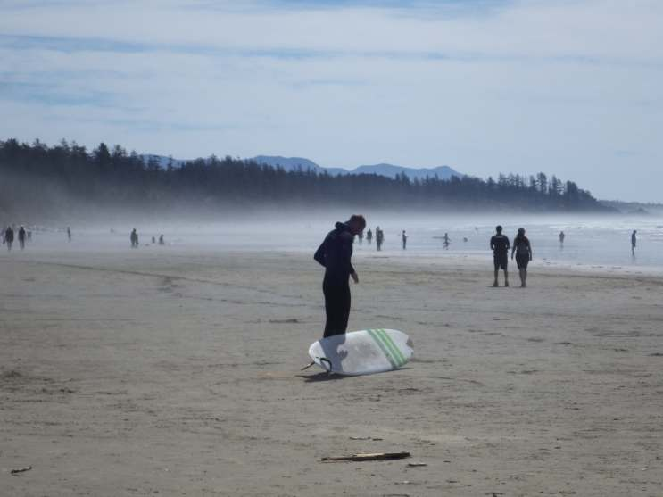 The mists off the sand while a surfer prepares
